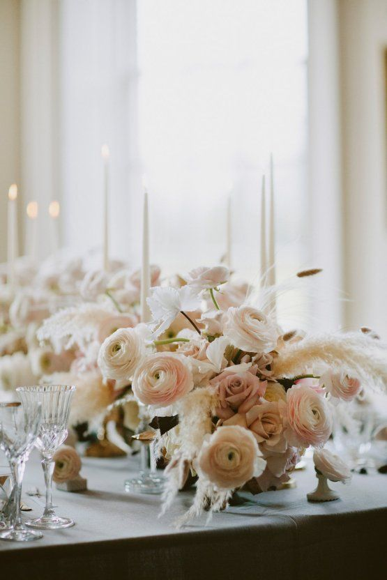 very refined and glam wedding centerpieces of ranunculus, blush roses and pampas grass plus white candles