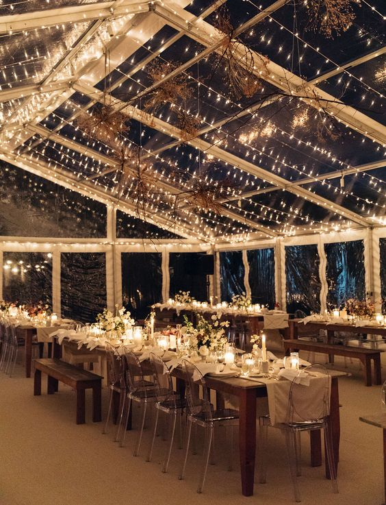 a modern fall wedding reception with ghost chairs and woodne benches, with a light canopy and neutral blooms