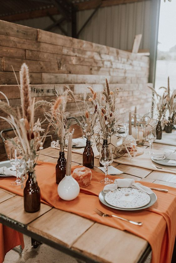 a simple and pretty boho wedding tablescape with rust placemats, grasses in bottles, quartz candleholders is chic