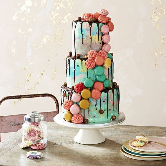 a super bold and colorful wedding cake with chocolate drip, colorful macarons and meringue roses is amazing