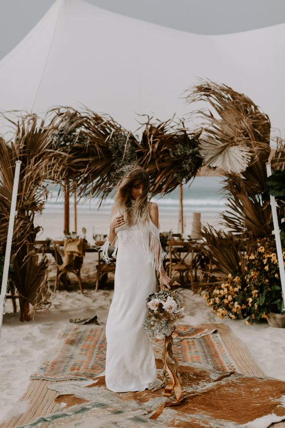 a wedding tent framed with dried palm leaves and bold blooms and greenery is a bold idea for a boho wedding