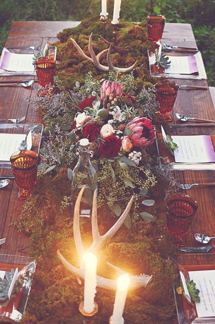 a woodland Nordic tablescape with a greenery and moss runner, bold blooms, antlers and candles plus amber glasses