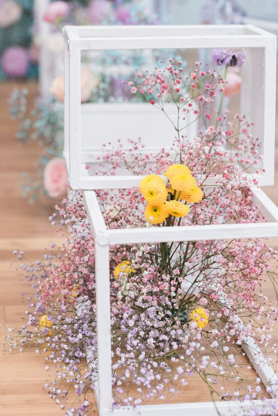 wedding decor with white cubes and pink and lilac baby's breath and yellow blooms is very modern and cool