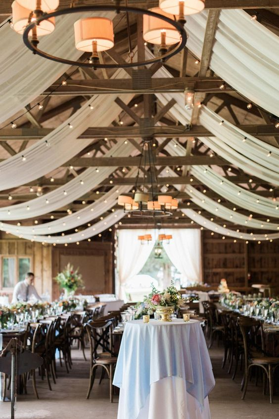 a modern rustic indoor wedding reception space with white fabric and light canopy is a pretty and chic idea