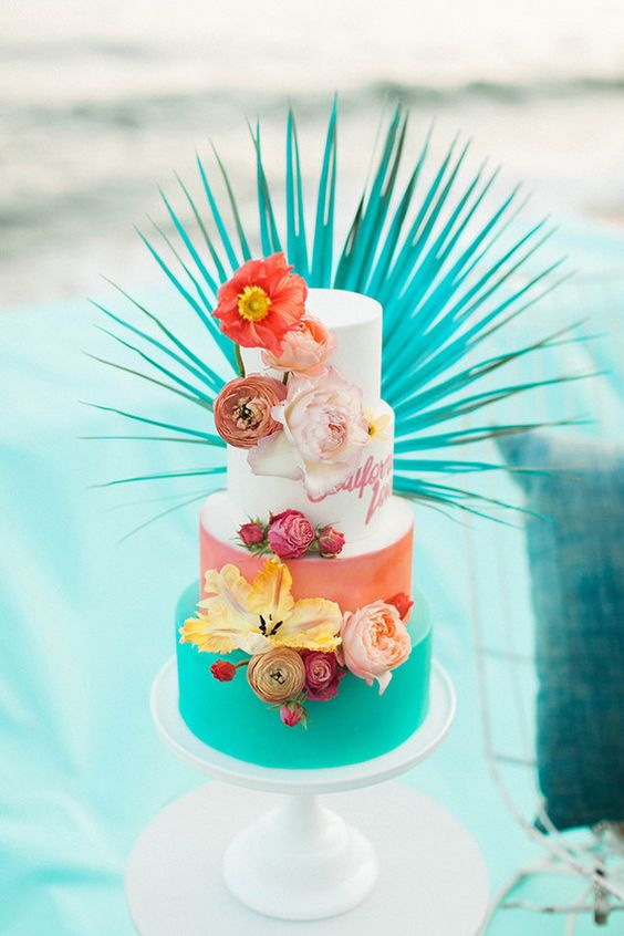 a super bold tropical wedding cake with a coral, blue, white painted and white tier, bright blooms and a spray painted frond