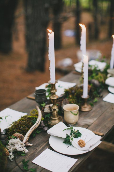 a woodland Scandinavian wedding table with a moss runner, pinecones, antlers, candles and greenery and nuts on the plates