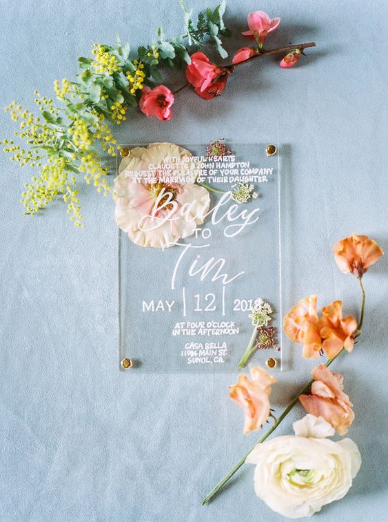 an acrylic wedding invitation with some pressed dried blooms is a very stylish and refined idea to rock