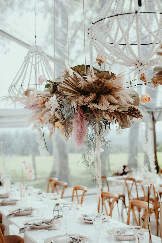 an overhead installation of dried fronds, colorful pampas grass, peachy blooms and green leaves looks statement-like