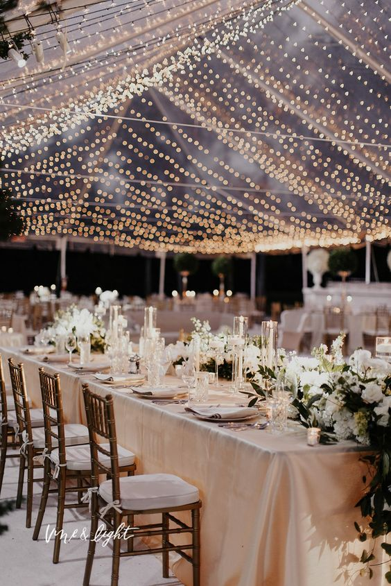 a stunning and elegant wedding reception done in pastels, with neutral blooms and floating candles and a large light canopy