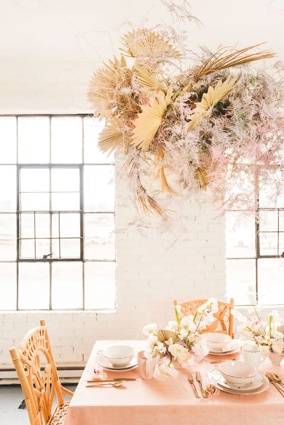 an overhead installation of yellow fronds, pink foliage and greenery is a gorgeous idea for a boho wedding