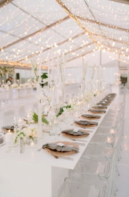 a stylish white, grey and gold modern wedding reception with a light canopy over the space and neutral blooms