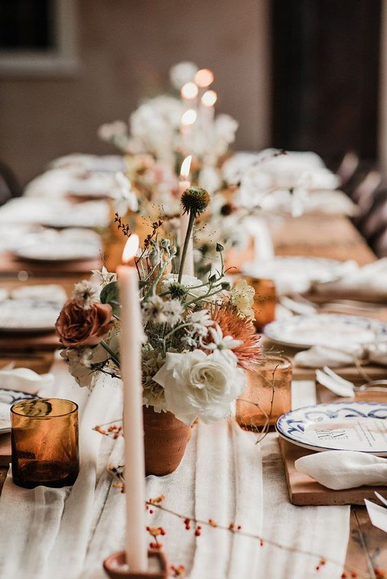 an airy and chic wedding table setting with a white runner and napkins, rust blooms, terracotta vases and amber glasses