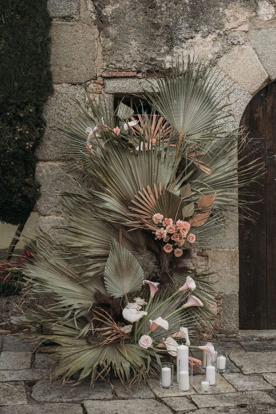 wedding decor done with fresh and dried palm leaves and pink and blush blooms plus candles on the ground is wow