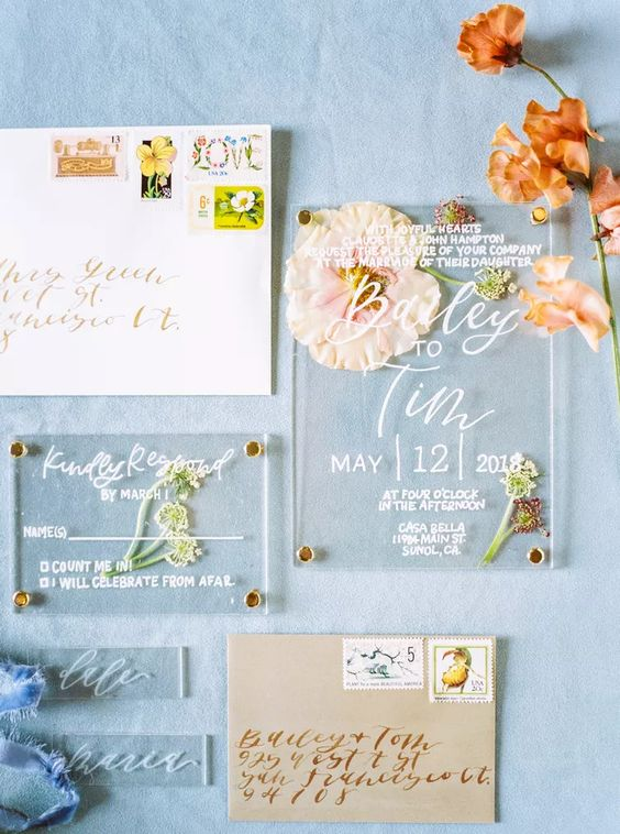 an acrylic wedding invitation suite with pressed blooms inside and neutral envelopes is a chic idea