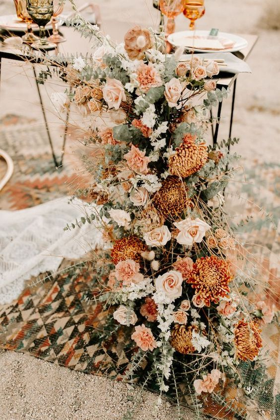an amazing wedding decoration with blush, rust, peachy blooms, eucalyptus and twigs is a cool for a boho wedding