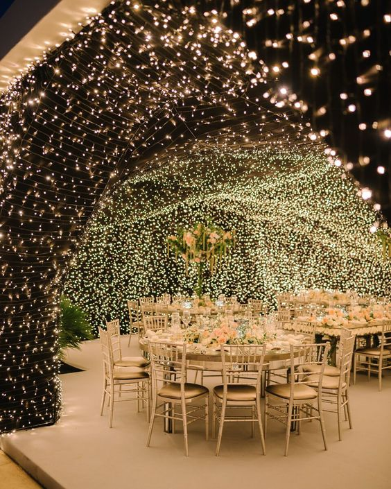 an indoor wedding reception with lights covering all the walls and ceiling turning the space into a magical cave