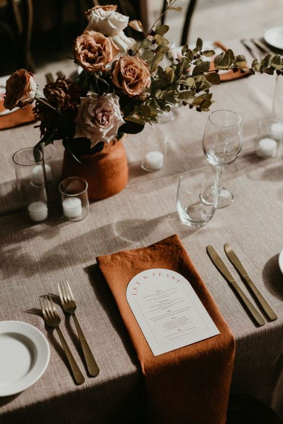 an elegant wedding tablescape with a terracotta vase with rust and blush blooms and greenery, white candles, rust napkins