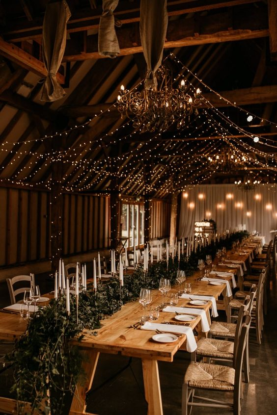 an intimate rustic wedding reception with a greenery runner with candles and a light canopy over the table and with chic chandeliers