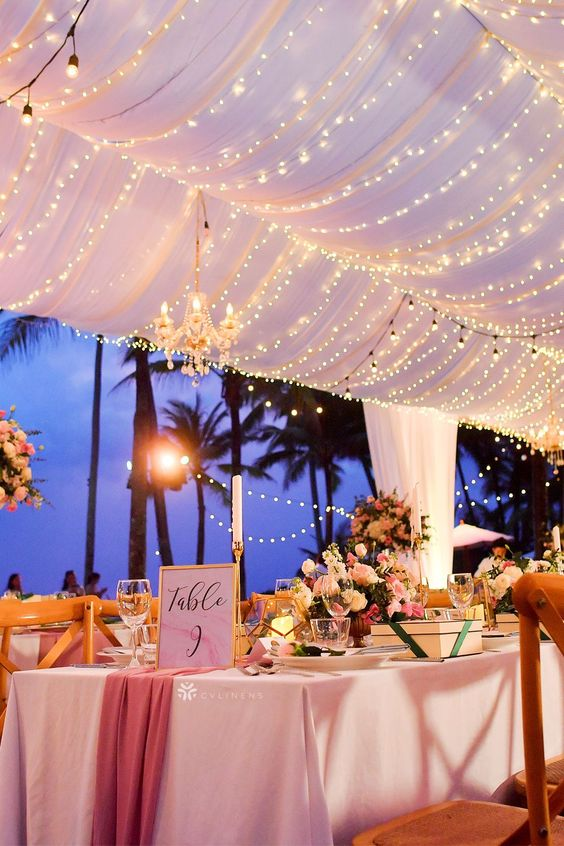 an outdoor wedding reception with bright florals and with a fabric and light canopy over the space for a mood