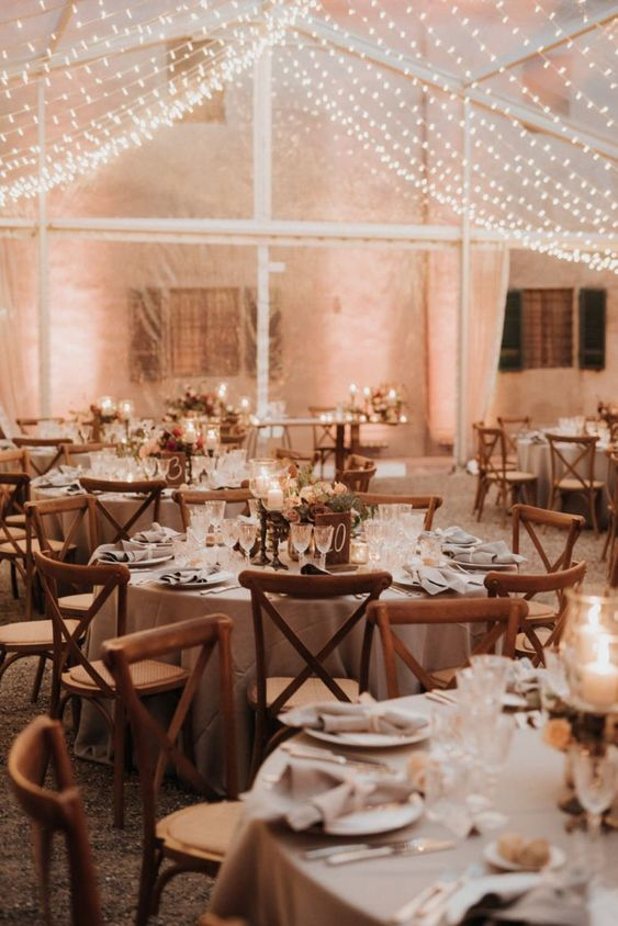 refined and chic indoor wedding reception space with neutral blooms and candles and a white light canopy over it
