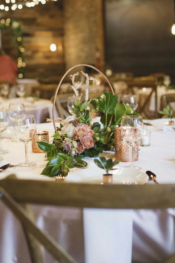 a beautiful hoop wedding centerpiece with foliage and pink, mauve and white blooms and candles around