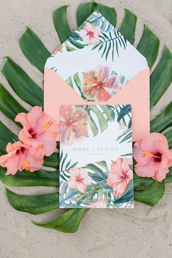 a blush envelope with tropical flower and leaf printing and a matching invitation for a glam tropical wedding
