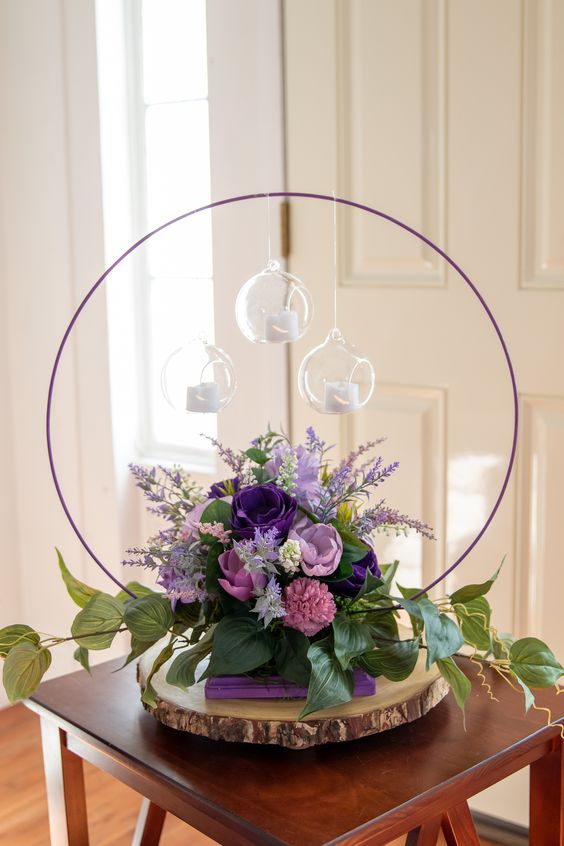 a bold hoop wedding centerpiece with purple, lilac and pink blooms, greenery and candles hanging over the florals