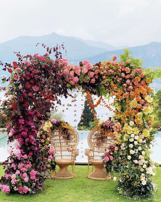 a bold lush floral wedding arch from light pink to mauve, burgundy, peachy pink, orange and yellow florals is a statement idea
