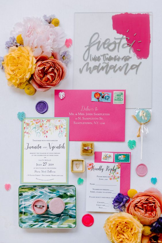 a bold modern tropical wedding invitation suite with hot pink envelopes, florals, an acrylic invitation is a cheerful and bold idea