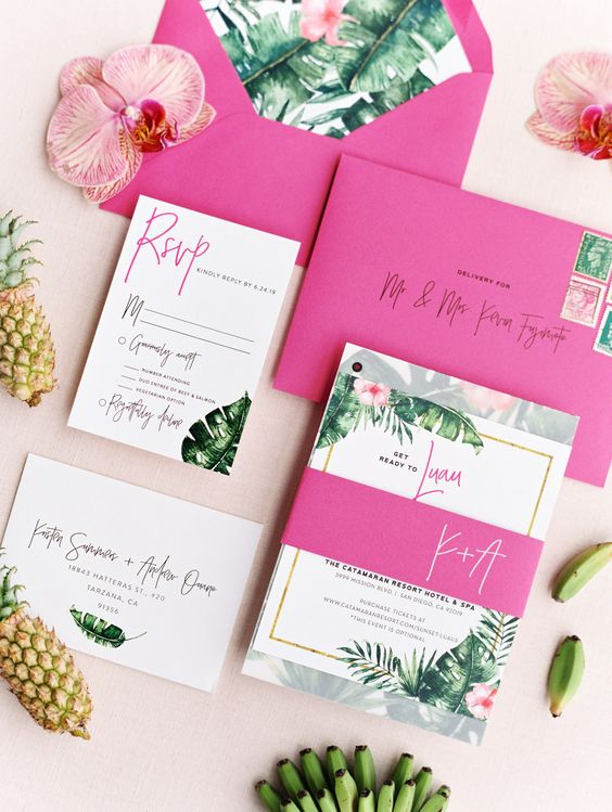 a bold tropical wedding invitation suite with hot pink envelopes, bold tropical leaves and blooms is a pretty modern idea