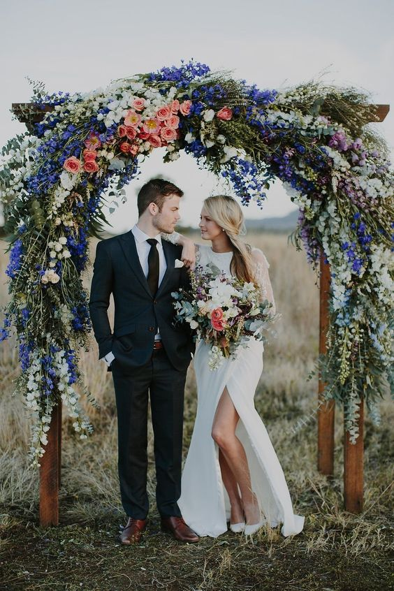 a bright and chic wedding arch with white, blue, pink and peachy pink blooms and eucalyptus is a gorgeous idea for decorating