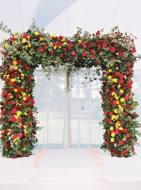 a bright and lush wedding arch of much greenery, deep red and burgundy blooms and yellow ones plus hanging branches