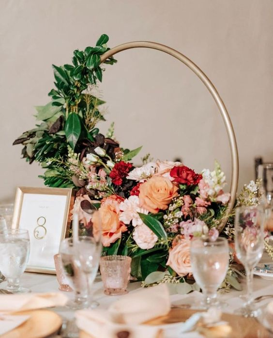 a bright and pretty hoop wedding centerpiece with lush greenery, blush, orage and red blooms is a lovely idea to go for