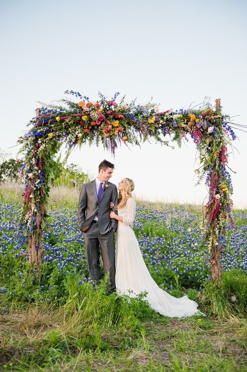 a bright floral wedding arch done with foliage and bold blooms of various shades is a veyr creative and bold idea