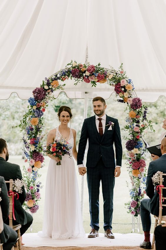 a bright floral wedding arch with lilac, yellow, blush, pink, orange and white blooms and some greenery is very chic
