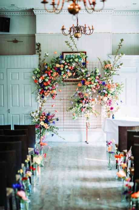 a bright floral wedding backdrop of greenery and colorful floral arrangements and matching floral arrangements to line up the aisle