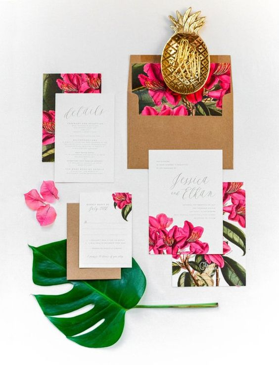 a bright tropical invitation suite with bold floral prints, leaves and kraft paper envelopes and calligraphy