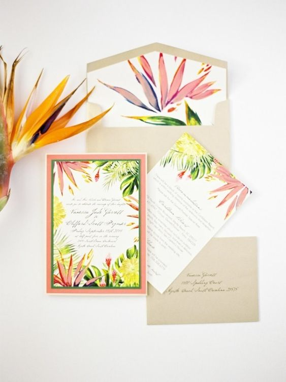 a cheerful tropical wedding invitation suite with bold tropical botanical prints and neutral grey envelopes