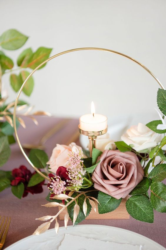 a chic hoop wedding centerpiece with deep red, mauve and blush roses, greenery and a candle plus gilded leaves