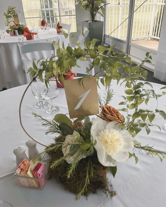 a chic hoop wedding centerpiece with greenery, white and coffee blooms and moss on the table is wow