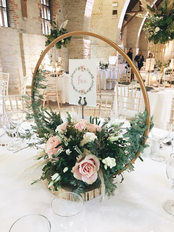 a chic hoop wedding centerpiece with greenery, white and light pink blooms and cards placed on a wood slice