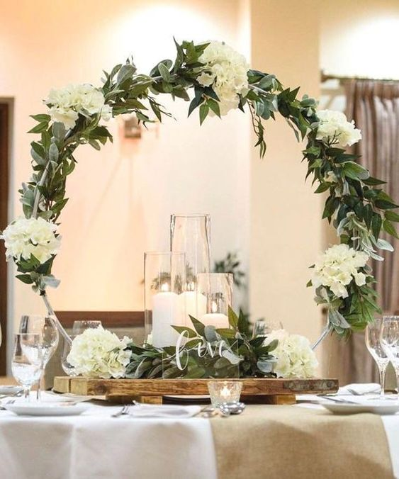 a chic large hoop wedding centerpiece with greenery and white hydrangeas plus candles in the center and candles around