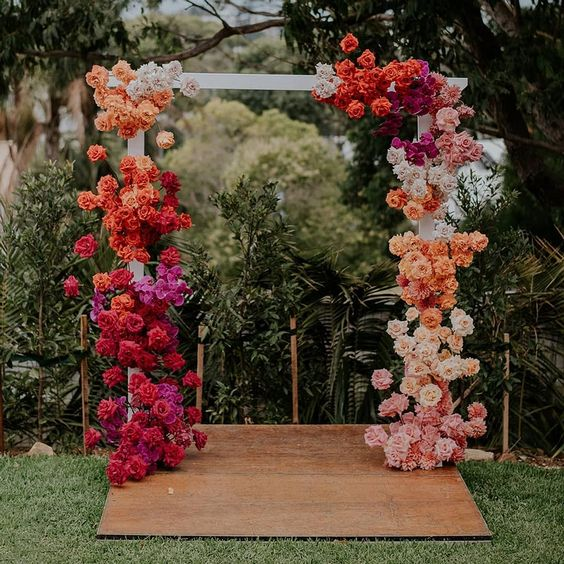 a colorful floral wedding arch with blooms of hot pink and light pink, red, orange, white, peachy pink colors looks spectacular