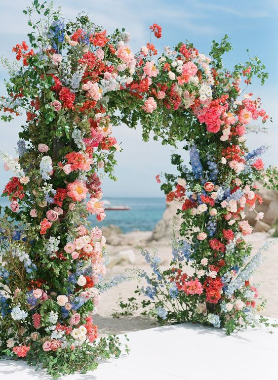 a colorful floral wedding arch with much textural greenery, pink, coral, blue and white blooms is an amazing solution for a coastal wedding