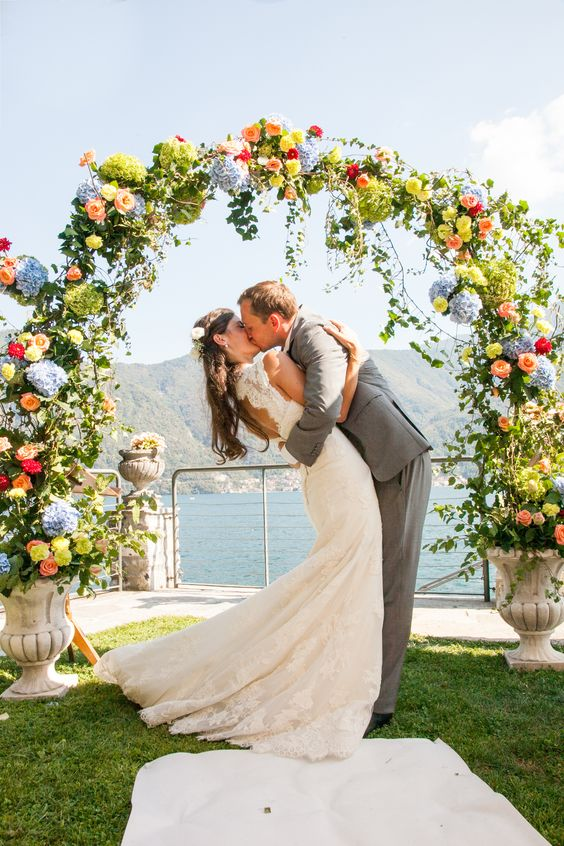 a colorful round wedding arch coming out of vintage urns, with greenery, green, blue, yellow, peachy and red blooms makes a statement