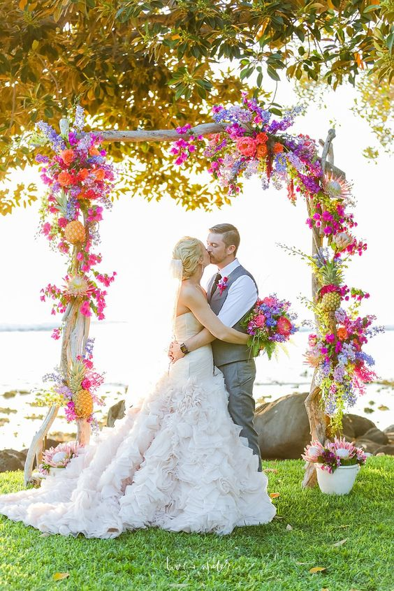 a cool tropical floral wedding arch
