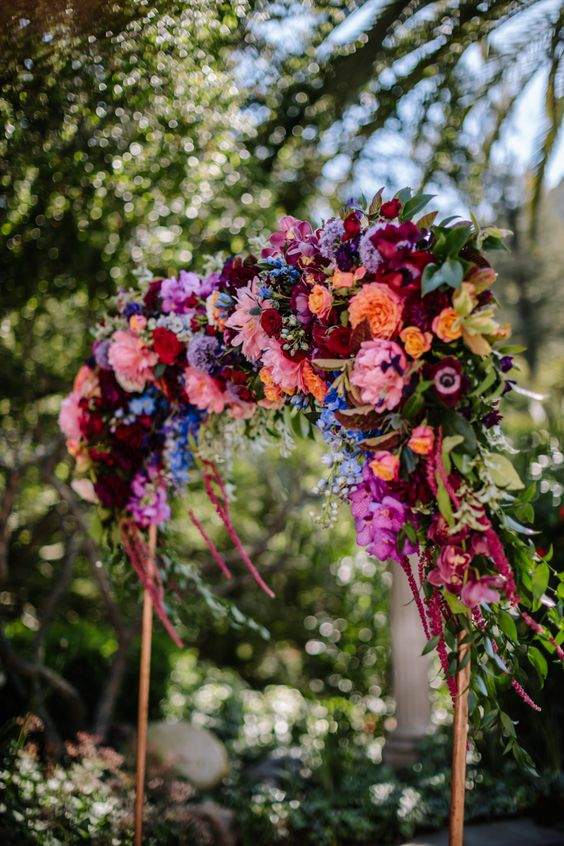 a colorful wedding arch in jewel tones - burgundy, deep red, orange, yellow and pink blooms and greenery is a chic idea for a fall wedding
