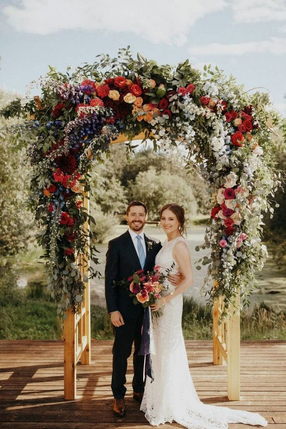 a colorful wedding arch with blooms of white, red, orange, purple, pink, burgundy and some textural greenery for a farmhouse wedding