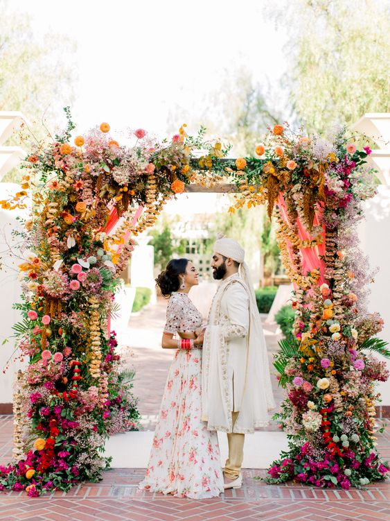 a colorful wedding arch with much greenery, bright florals and hanging ribbons and blooming branches for a bold wedding