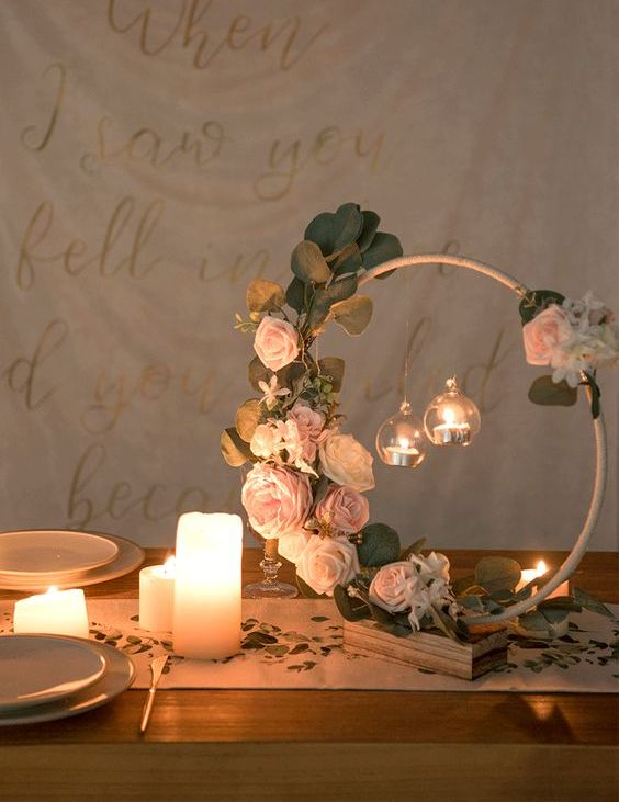 a delicate hoop wedding centerpiece with greenery, blush and light pink blooms and hanging candles